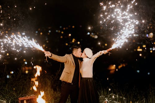 Stylish couple with fireworks at night