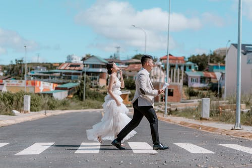 Happy ethnic newlyweds on road in city