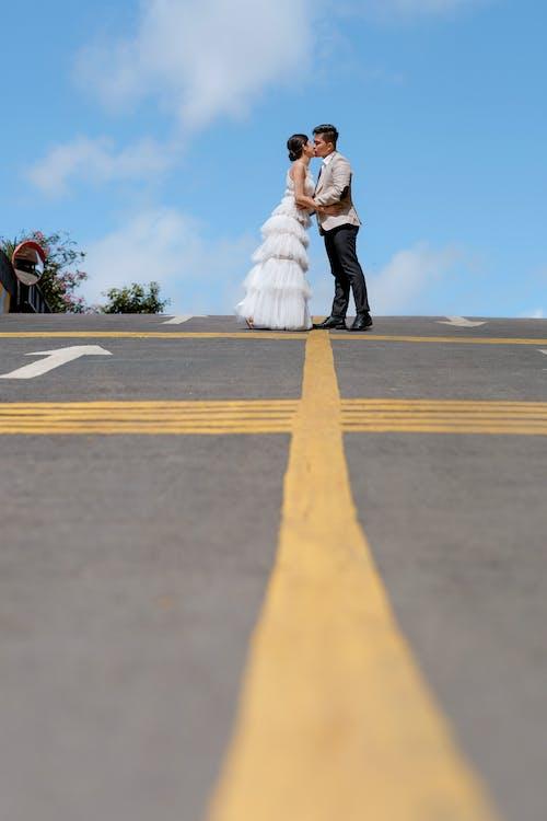 Stylish newlyweds on empty road in sunny day