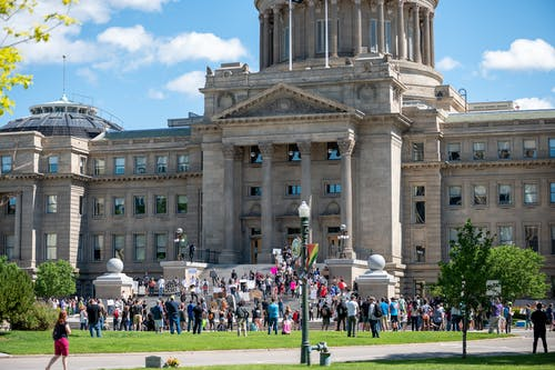People gathering outside majestic Idaho State Capitol building for meeting on sunny day in Boise City