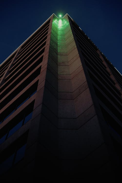 Low angle tall residential building corner with bright green light shining on top in dark night