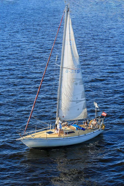 High angle of people on sail deck enjoying marine trip in sunny day in blue rippling sea