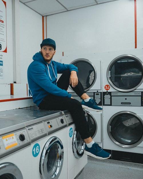 Uomo In Camicia A Maniche Lunghe Blu E Pantaloni Neri Che Si Siede Sulla Lavatrice A Carico Frontale