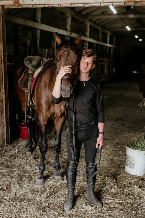 Woman in Black Leather Jacket Standing Beside Brown Horse