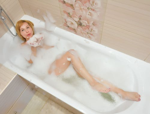From above of satisfied female lying in bath and blowing foam while having rest at home
