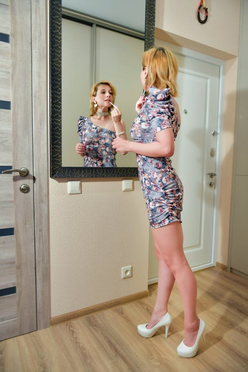 Full body of pensive female in casual clothes and high heels looking at mirror and painting lips