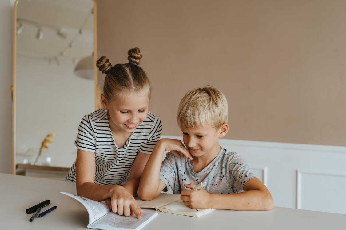 Sister Helping her Brother with Homework