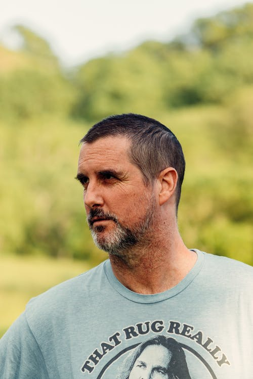 Serious bearded middle aged male in casual shirt standing against blurred lush green trees and looking away thoughtfully