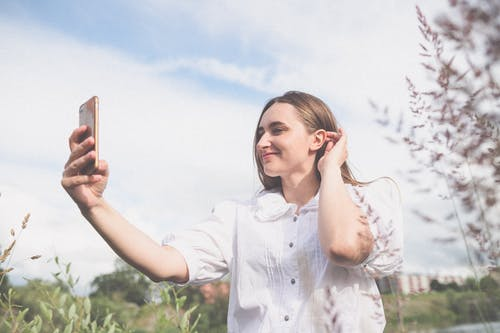 Close-Up Shot of a Pretty Woman in White Blouse Taking Selfie Using a Smartphone