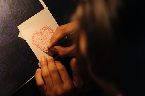 Close-Up Shot of a Person Writing on a White Paper Using a Colored Pencil