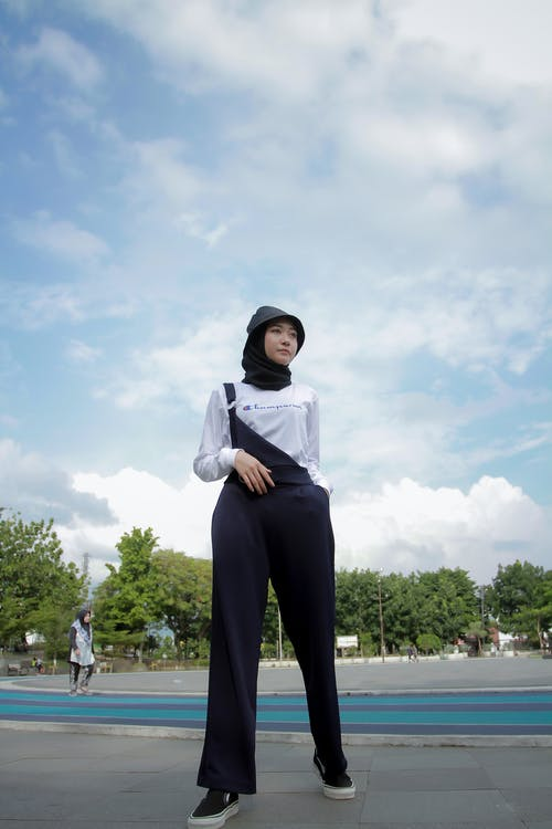 Woman in White Hijab and Black Pants Standing on Gray Concrete Floor