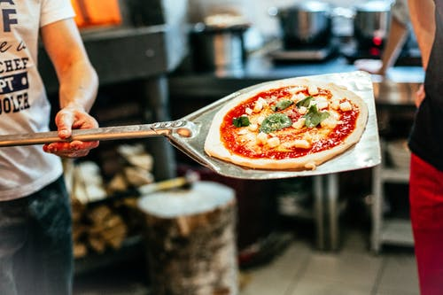 Person Holding Stainless Steel Spoon With Sliced Pizza