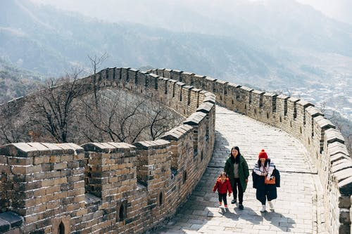 People Walking on Concrete Brick Wall