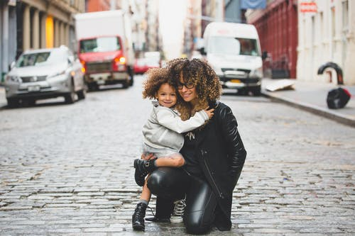 Woman Wearing Black Jacket Holding Girl