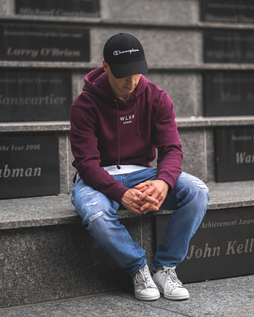 Man in Brown Hoodie and Blue Denim Jeans Sitting on Concrete Bench