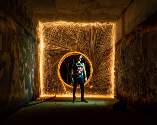 Man standing against lines of light in circle from fire swing