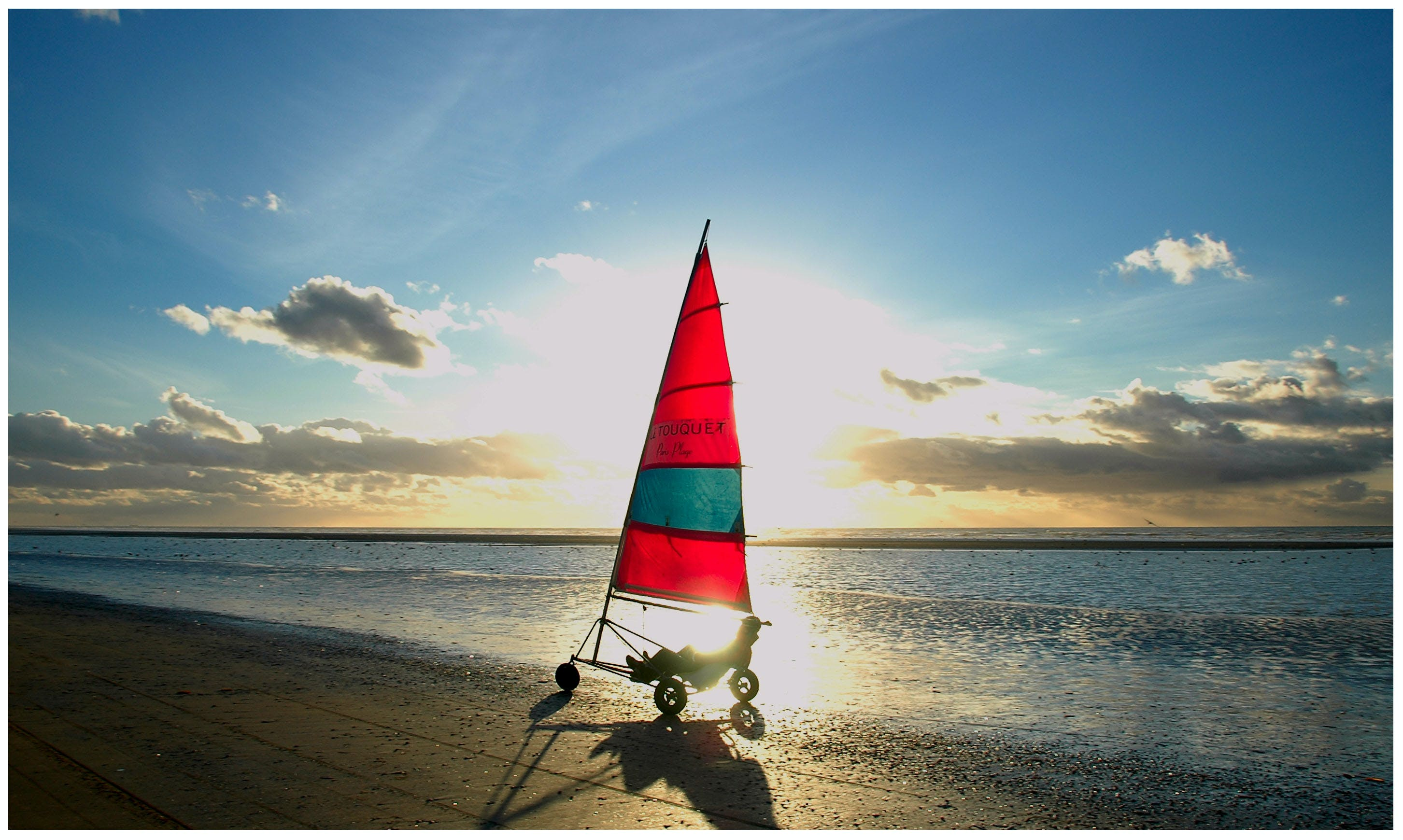 Man Riding Sailboat on Beach Sand