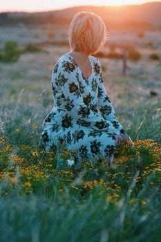Woman in White and Black Floral Themed Dress Sitting on Green Grass Field