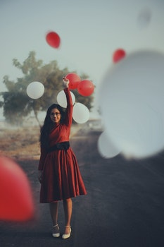 Woman in Red Midi Dress Holding Balloons