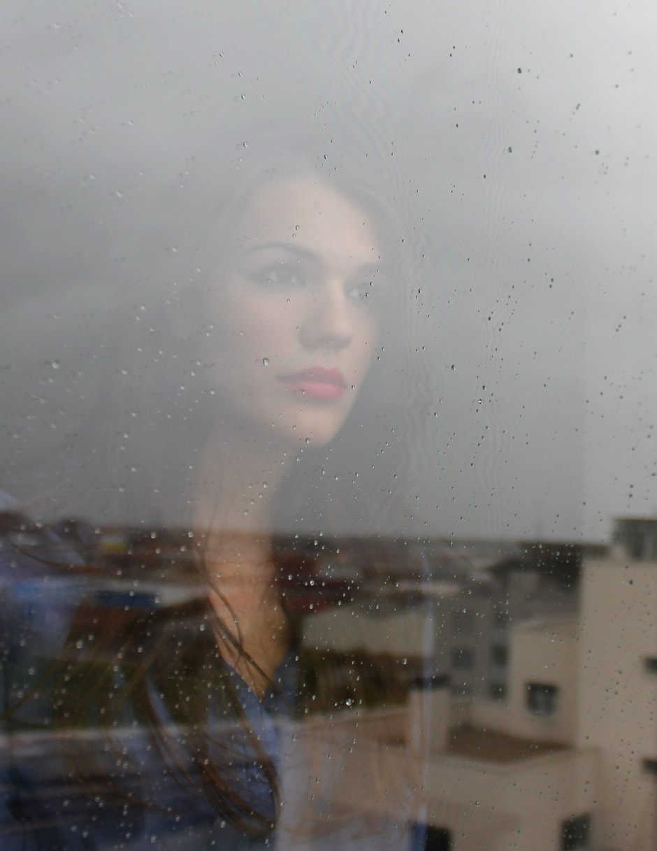 Woman Fronting Glass Window over Looking in Town