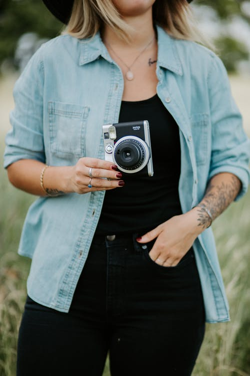 Woman in Blue Denim Jacket Holding Black and Silver Camera