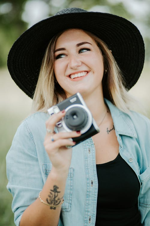 Smiling Woman in Blue Denim Jacket Holding Camera
