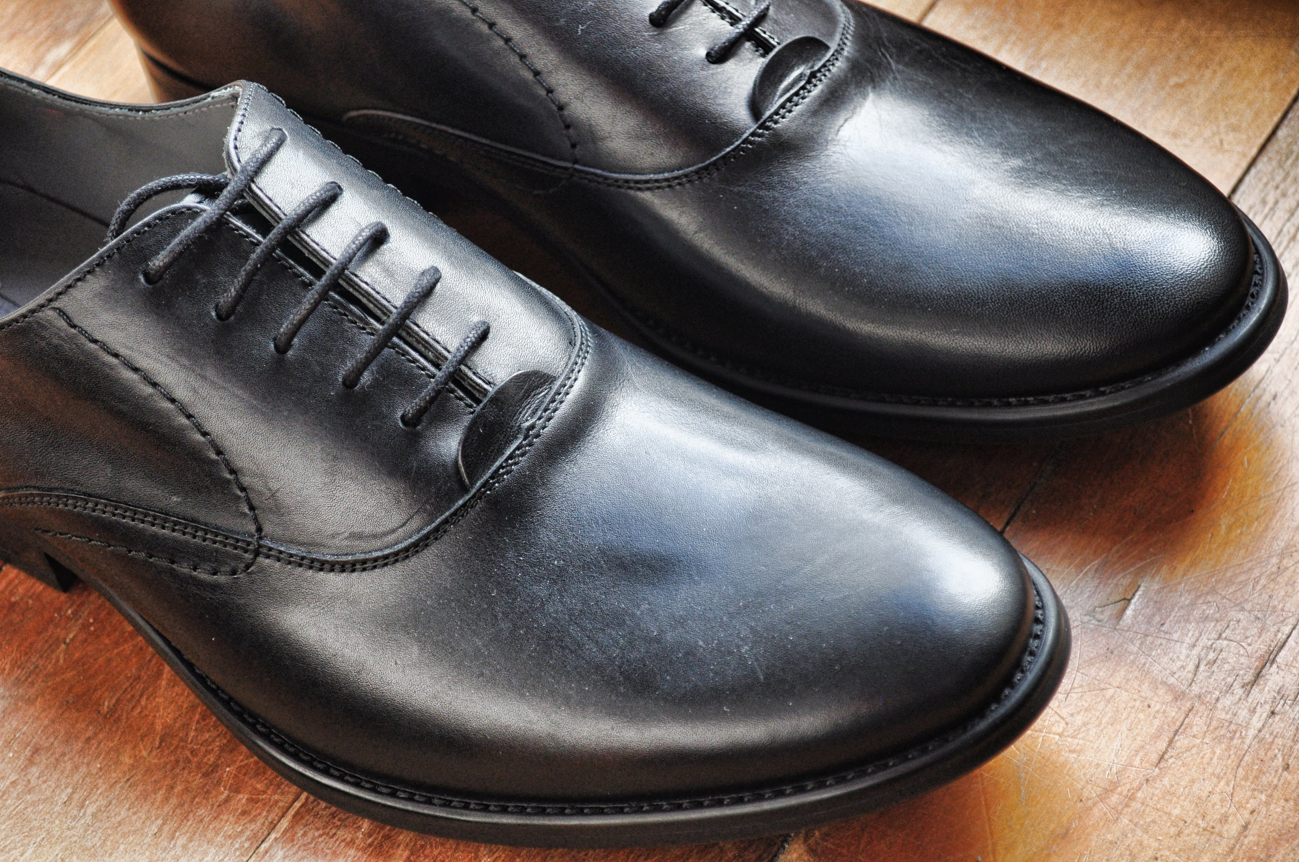 Black Leather Shoes on Brown Wooden Tile Floor