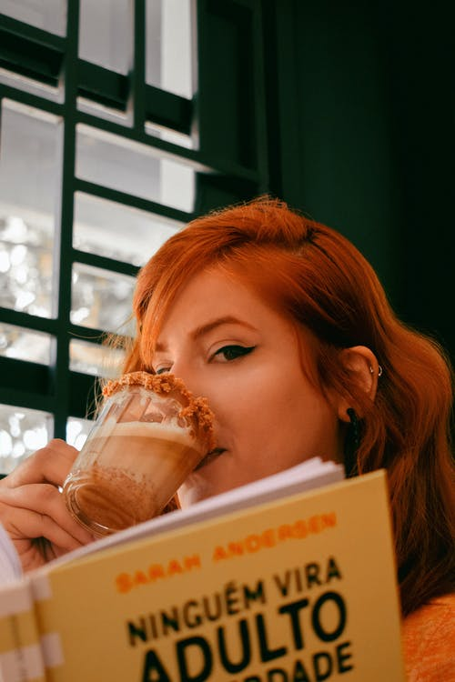 Woman Holding White and Brown Book