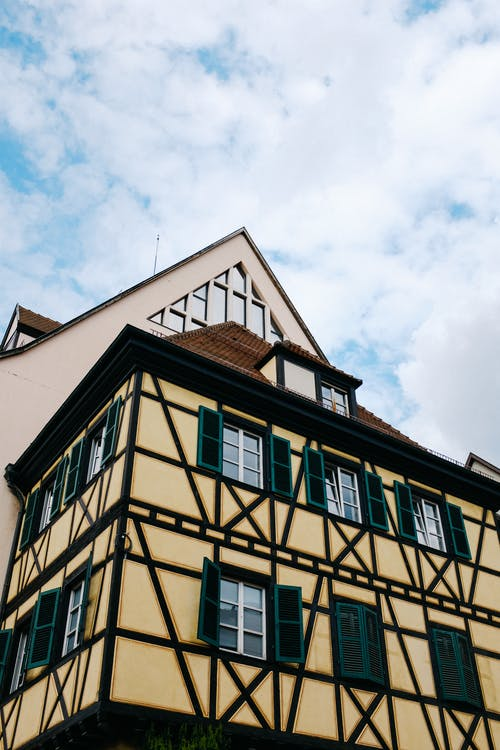 From below of half timbered house with yellow facade and small window on roof located in cloudy sky on street