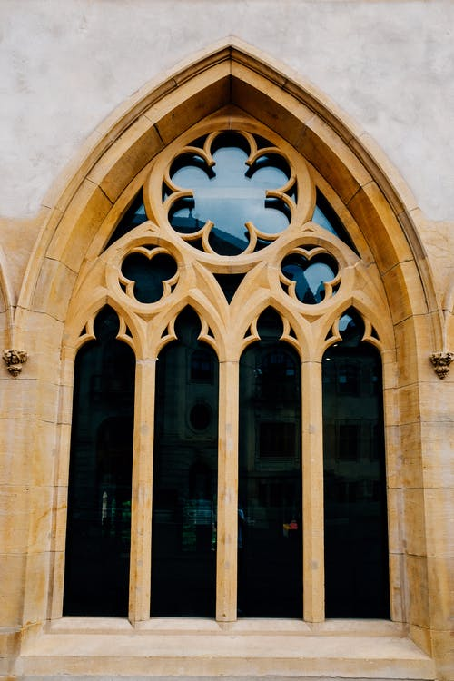 Low angle of arched stained glass window with ornamental elements of aged Gothic cathedral in daylight