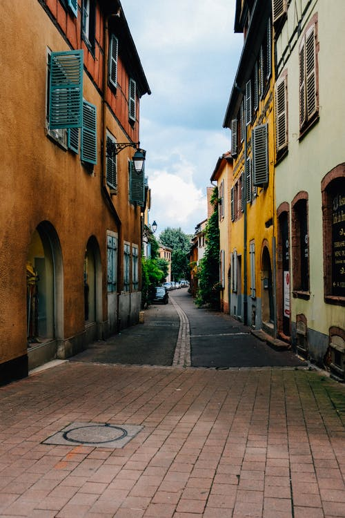Narrow paved street amidst colorful typical old residential buildings located in Colmar against cloudy sky
