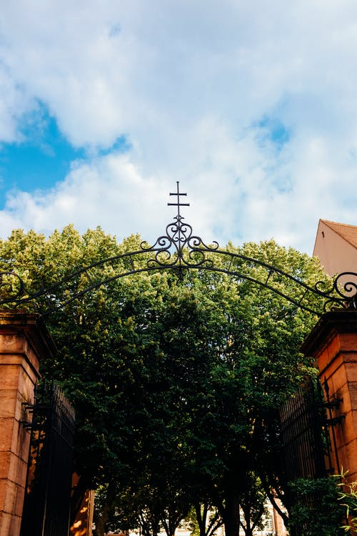 From below of forged cross on arched entrance of old church with lush green trees in yard against cloudy blue sky
