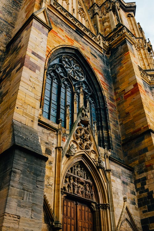 From below exterior of aged stone Saint Martin tower with arched window and wooden door located in Colmar city in France