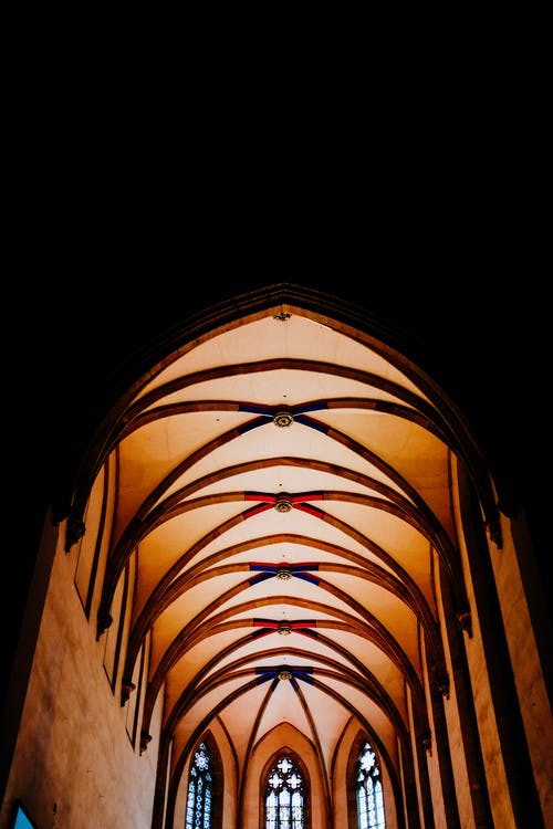 From below of catholic cathedral with arched entrance and round shaped ceiling with geometrical elements