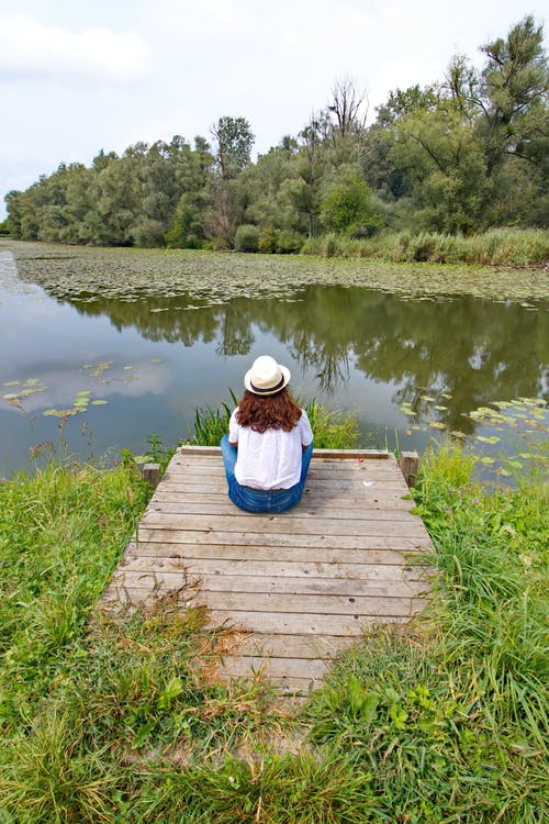 Back view of brunette in straw hat sitting alone on wooden pier looking at overgrown pond in summertime