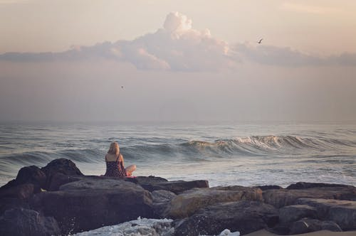 Woman Sitting on Rock Near Seashore