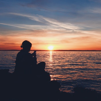 Person Sitting Rock during Sunset