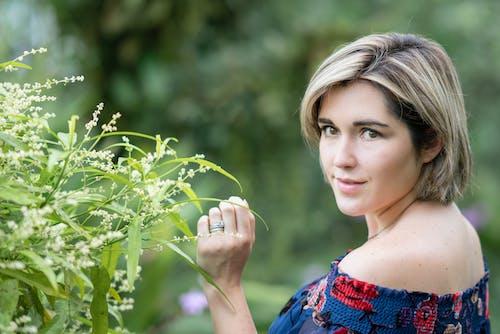 Pleased woman standing near bush