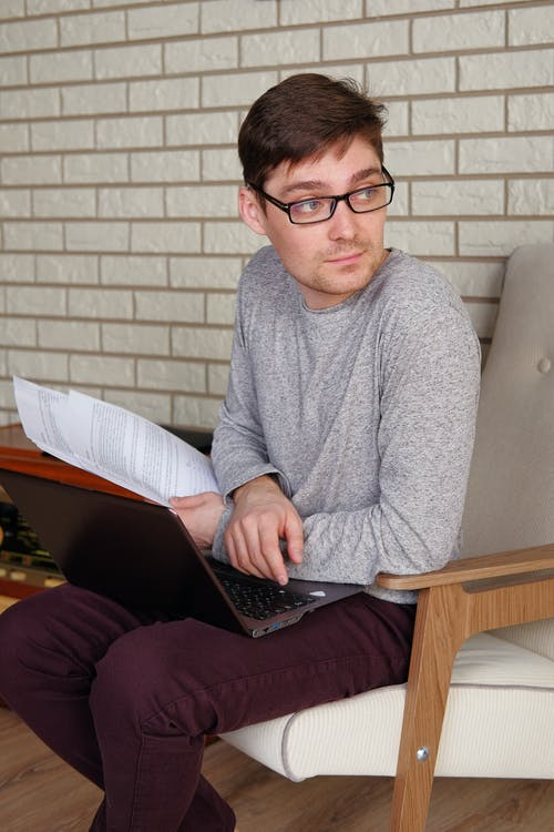 Pensive self employed man working on laptop from home