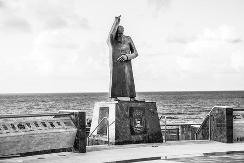 Grayscale Photo of Statue of Woman on Concrete Bench by the Sea