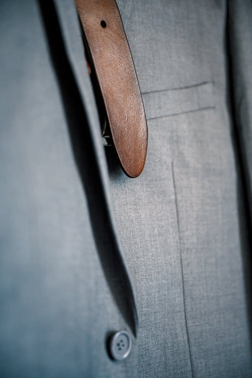 End of brown leather belt strip hanging with formal gray suit jacket in wardrobe