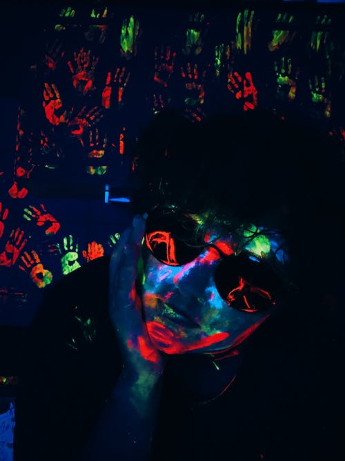 Serious male in sunglasses with colorful glowing neon paint on face in dark room with Uv lights