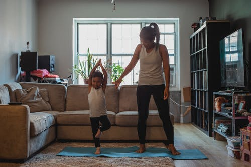 Full body positive mother teaching little kid to perform Tree Pose on mat in cozy living room at home