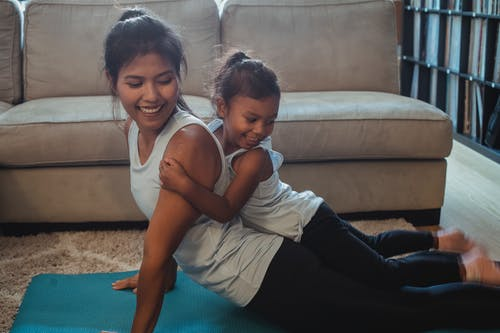 Happy ethnic girl lying on mothers back performing Cobra Pose