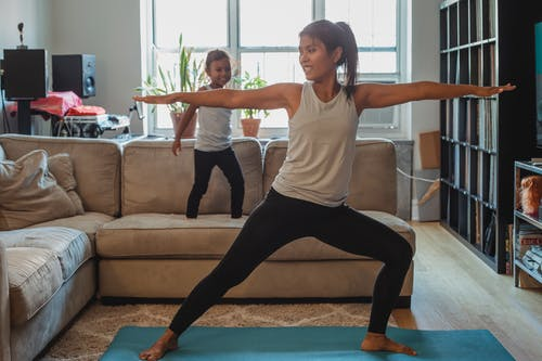 Full body barefoot cheerful female in sportswear standing in Warrior Pose on mat in living room near cute daughter walking on sofa