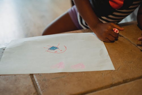Crop unrecognizable black child leaning on stone bench with drawing