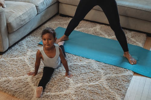 High angle flexible ethnic girl in sportswear doing splits on fluffy carpet near mother while training together at home