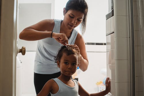 Young ethnic mother doing hair of cute daughter in bathroom