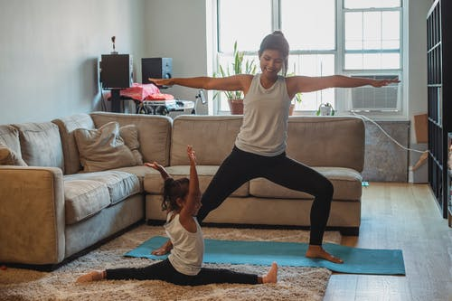 Full body cheerful ethnic mother in sportswear practicing yoga and performing Warrior Pose on mat near cute daughter doing splits in light living room