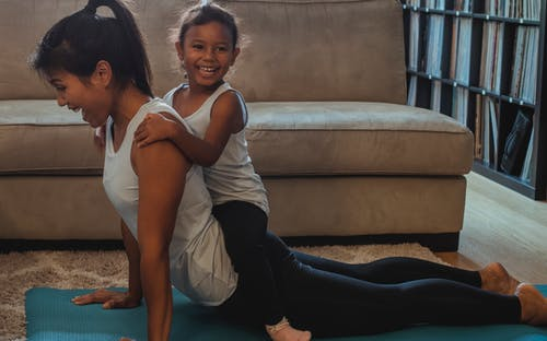 Side view laughing young ethnic female in sportswear performing Cobra Pose with cute smiling daughter on back while practicing yoga at home
